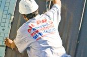 roofer wearing all pro roofing and remodeling inc shirt holding tape measure against steel roof