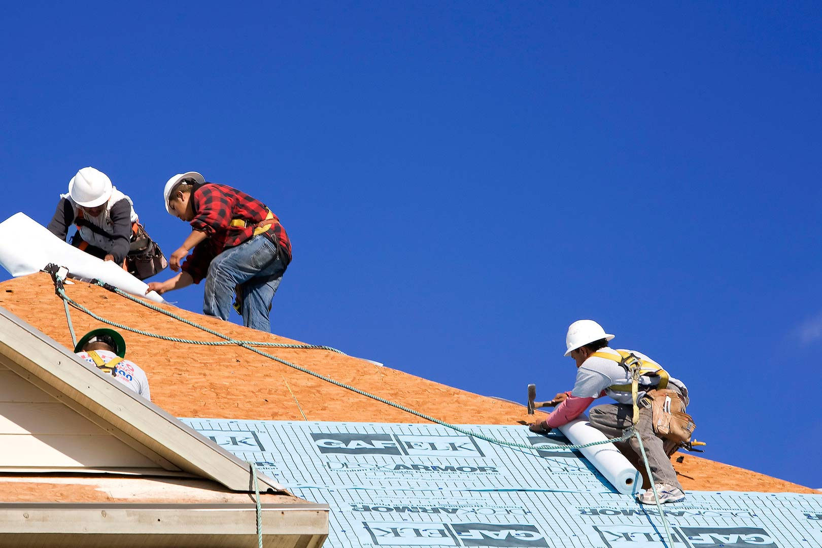 four roofers working on top of house with clear blue sky in the background