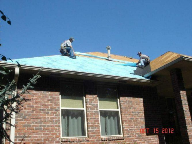 two men working on top of home roof