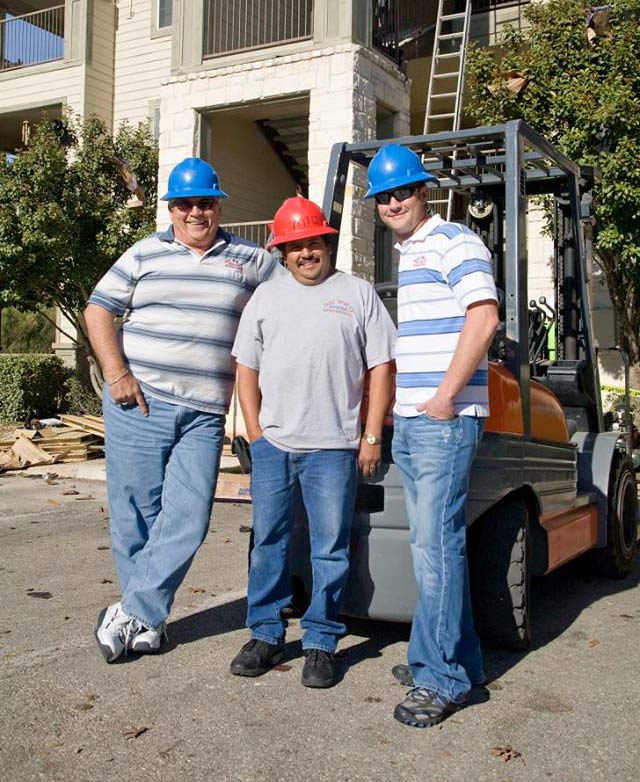 three smiling men wearing hard hats standing in front of forklift